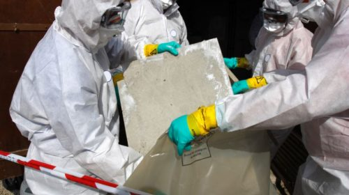 men in protective gear removing asbestos from a job site